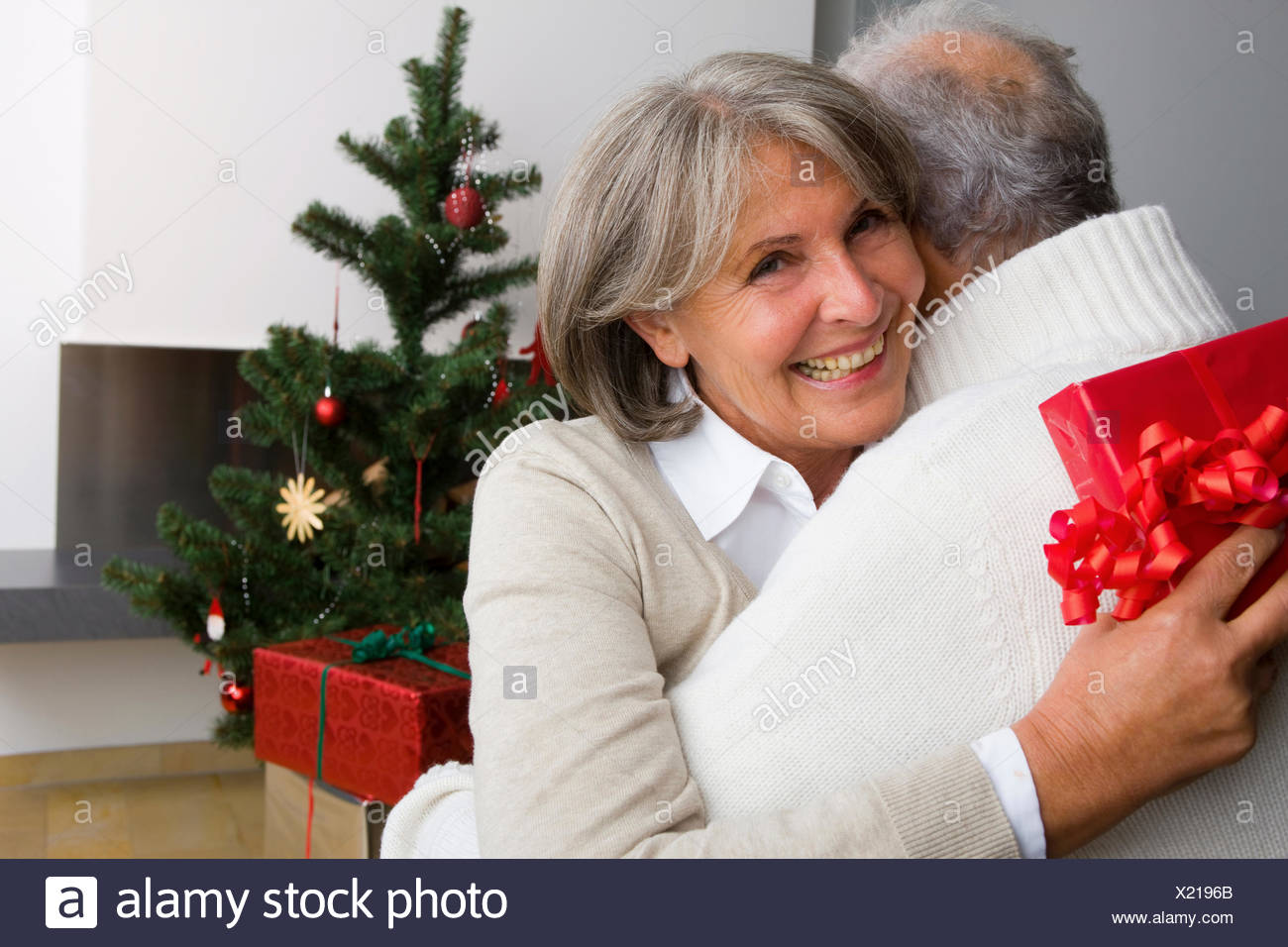 Senior couple exchanging Christmas presents at home Stock Photo