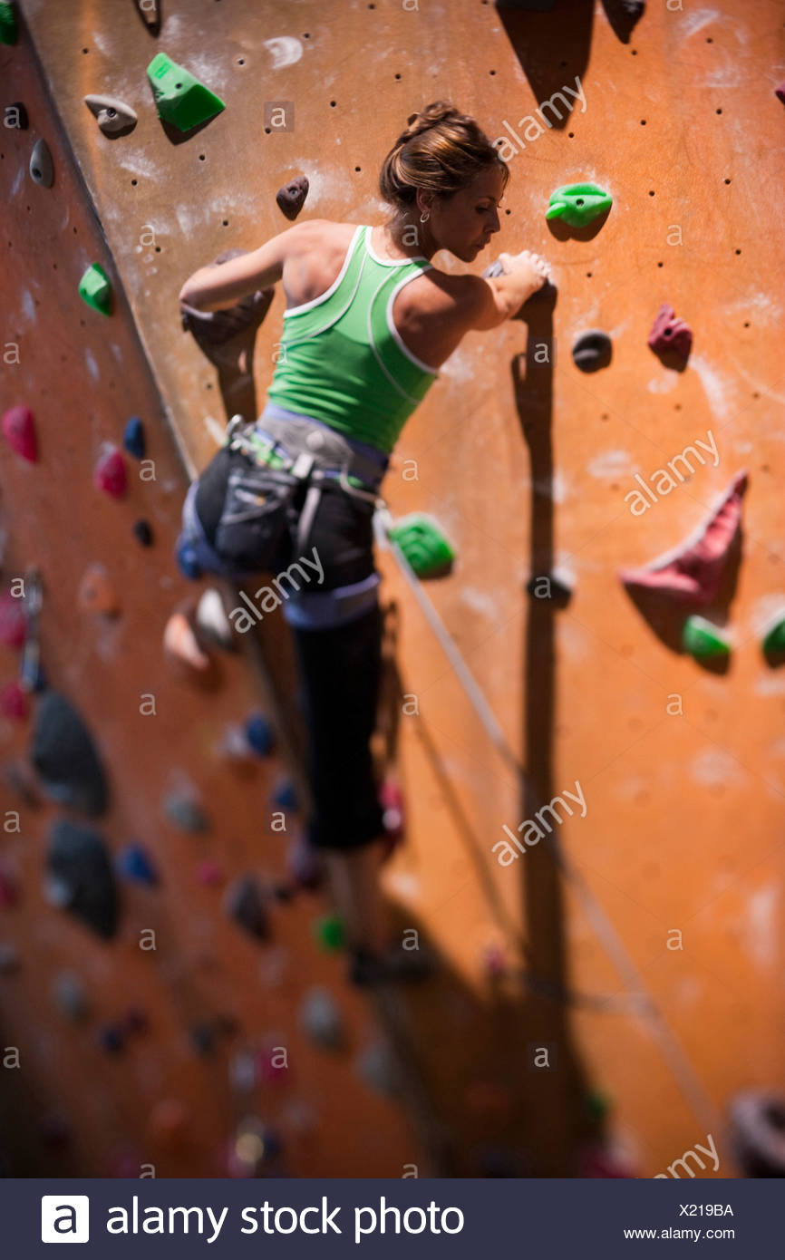 USA, Utah, Sandy, young woman on indoor climbing wall - Stock Image