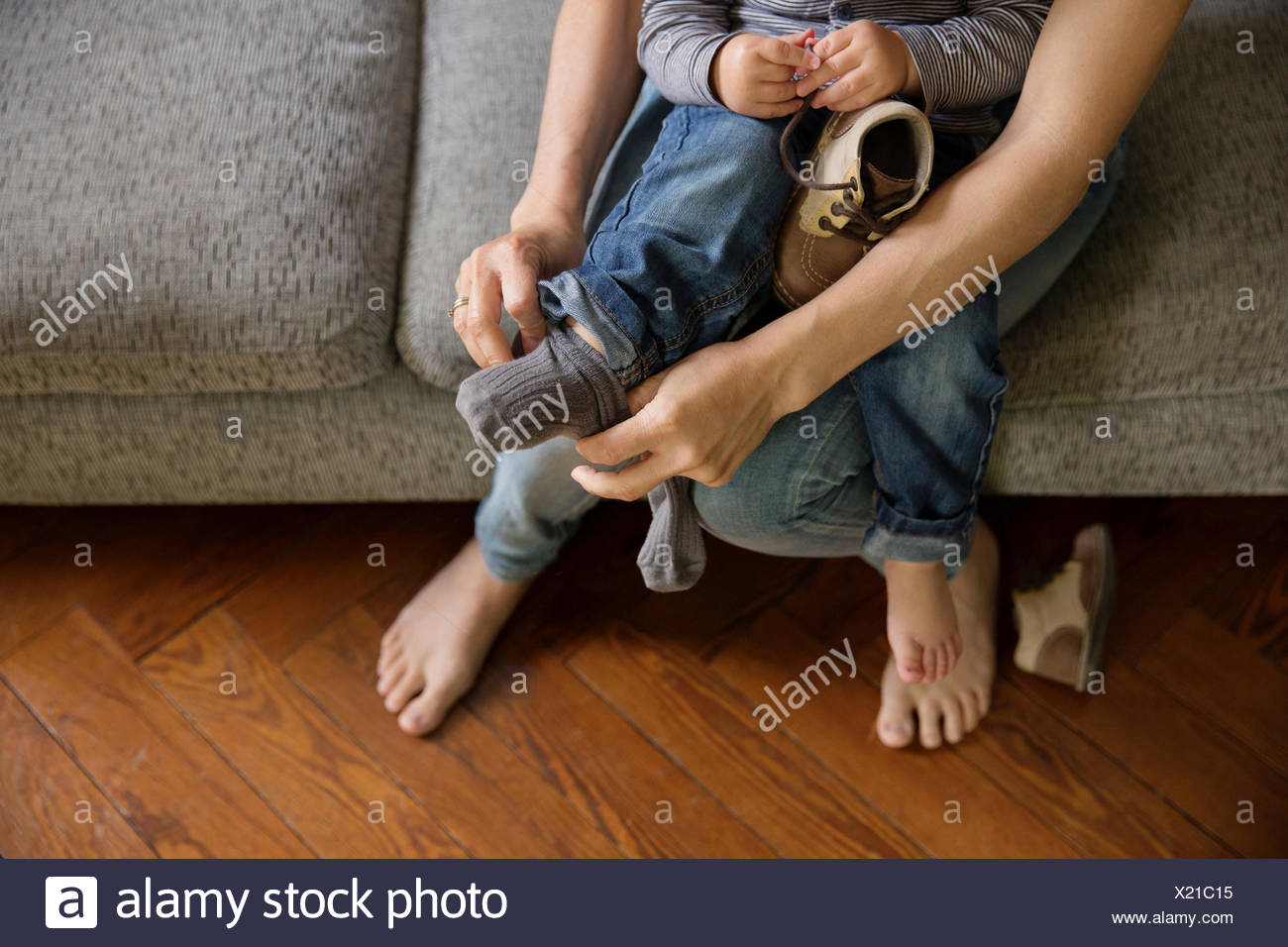 Mother's hands helping toddler putting his socks and shoes on - Stock Image