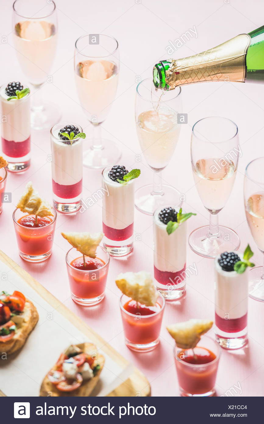 Various snacks, brushettas, gazpacho shots, desserts with berries and champagne pouring to glasses on corporate event, christmas, wedding celebration - Stock Image