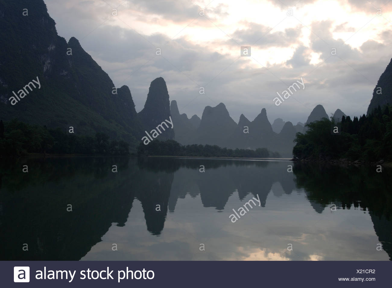 Scenic view of mountains and body of water at sunrise - Stock Image