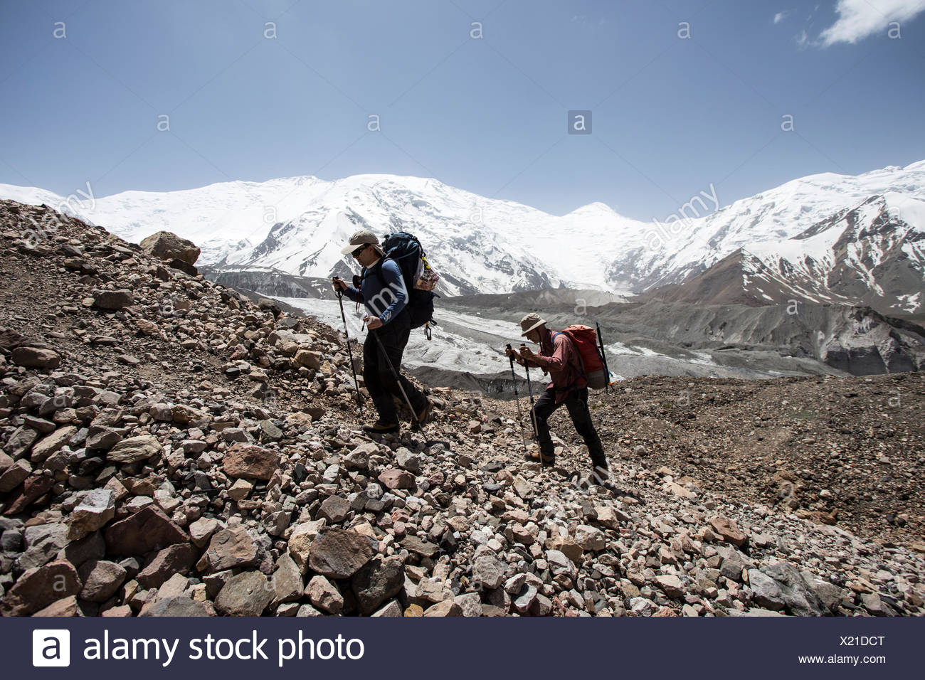 A couple of mountaineers in the approach to advanced basecamp of Peak Lenin Stock Photo