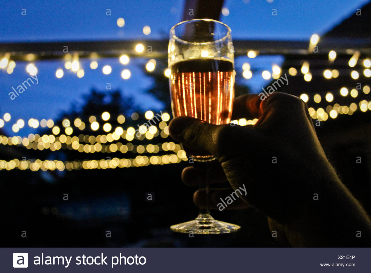 Hand Raising Champagne Flute - Stock Image