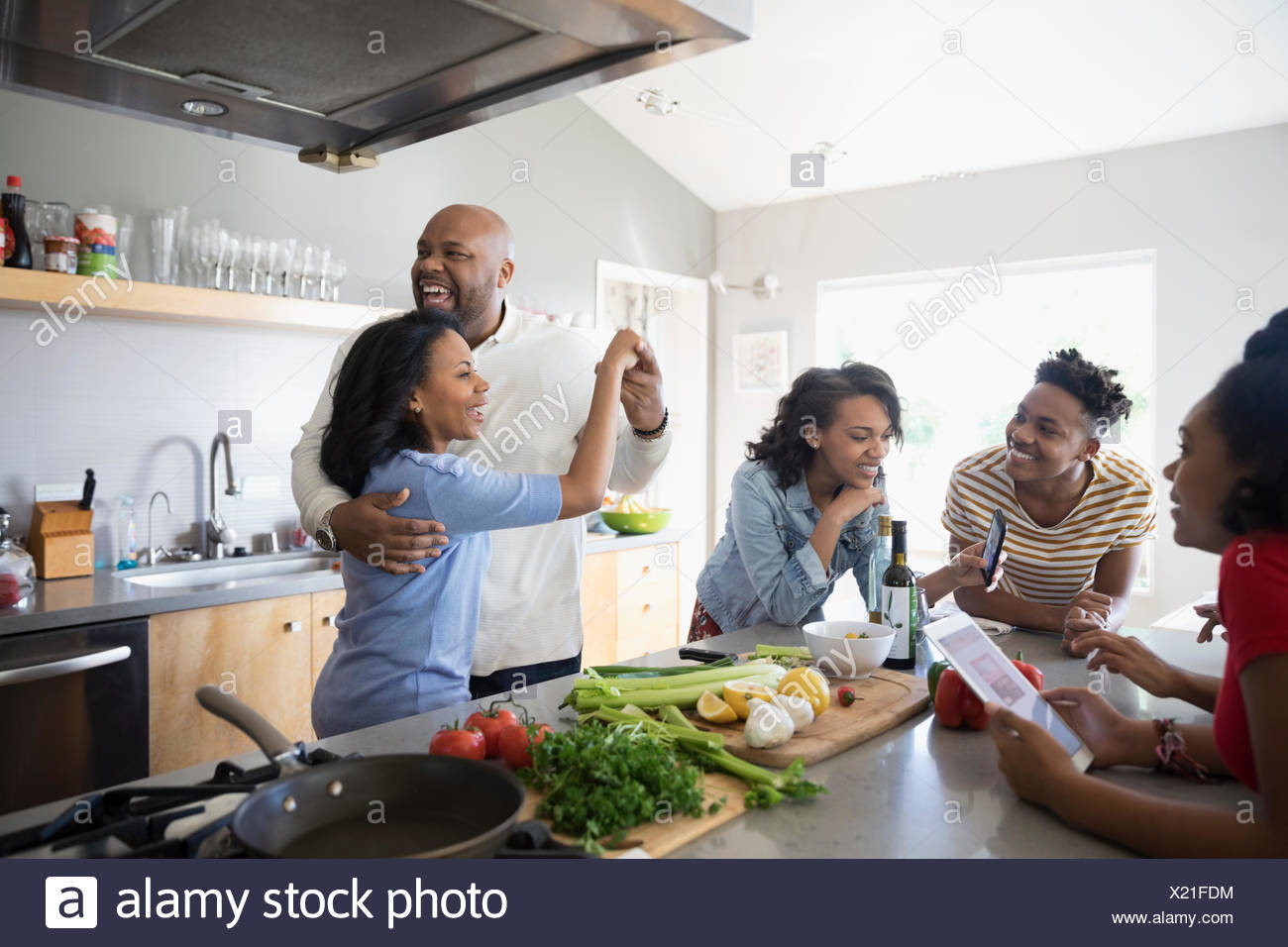 African American parents dancing and cooking with children in kitchen - Stock Image