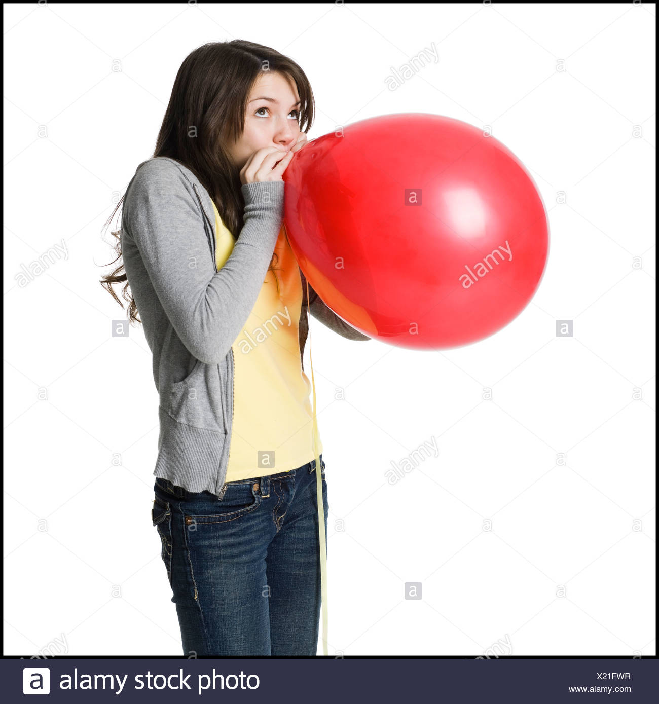 young woman blowing up a balloon - Stock Image