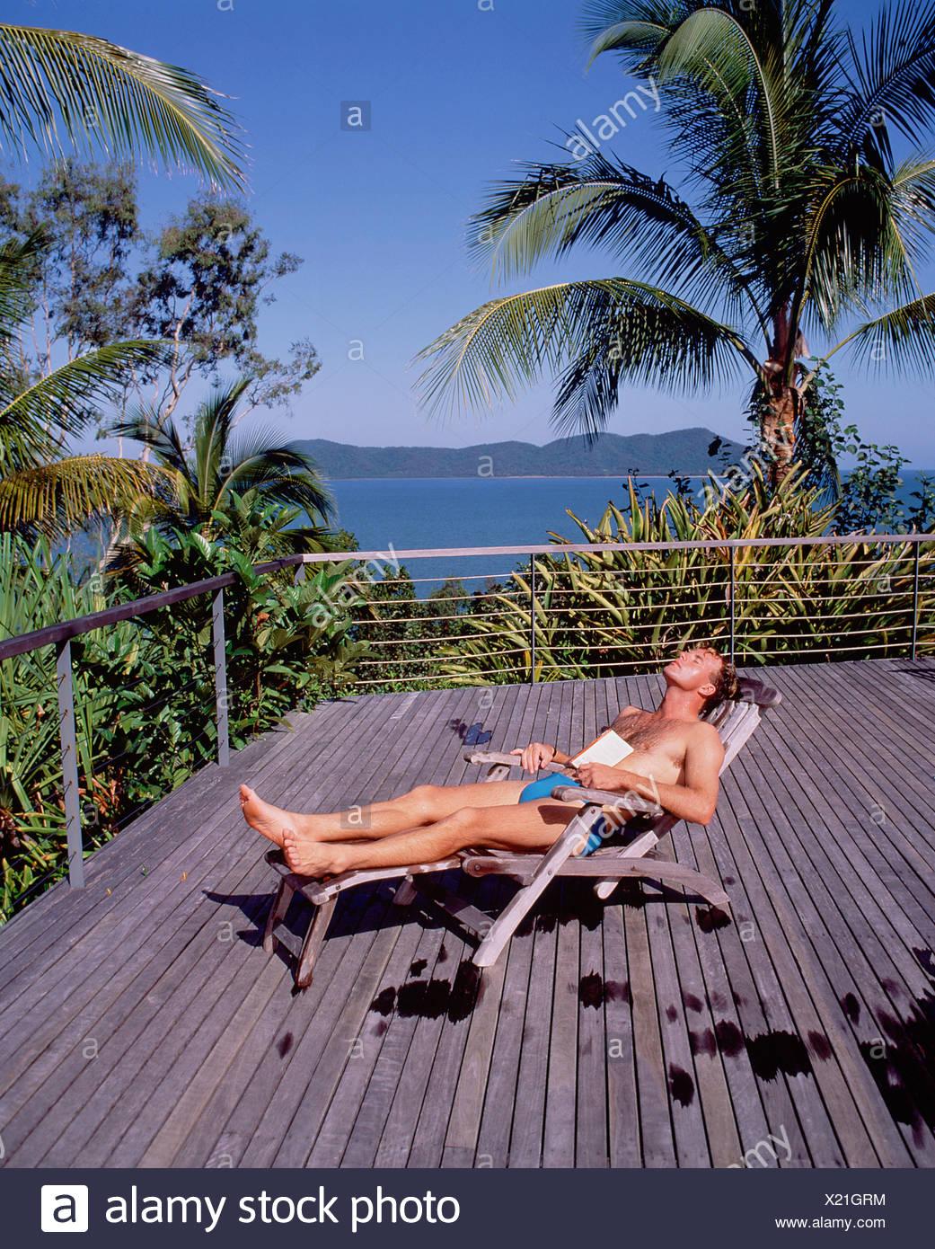 Young Man In Swimsuit On Recliner Chair In Terrace Deck. Queensland.  Australia.