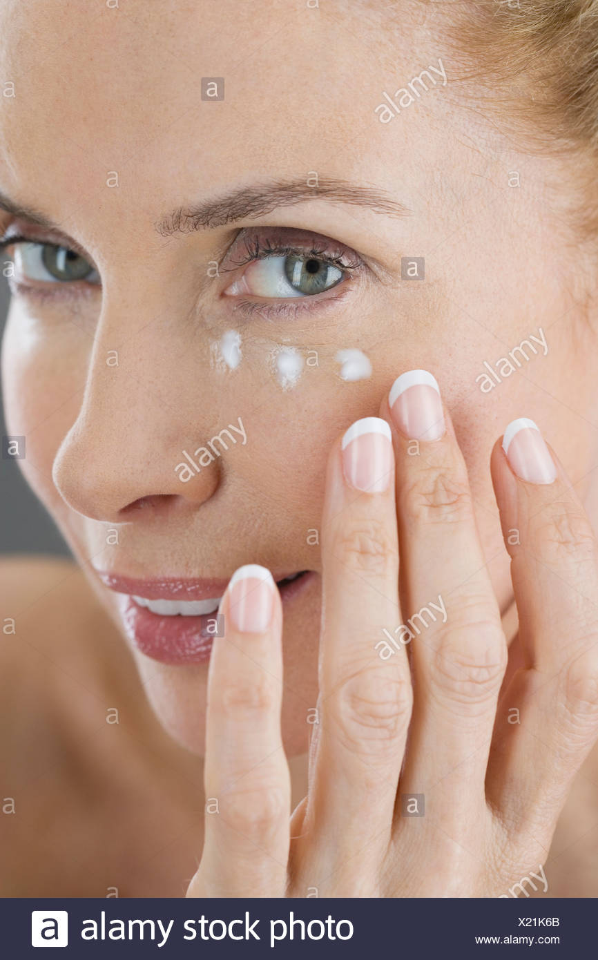 A middle-aged woman applying eye cream - Stock Image