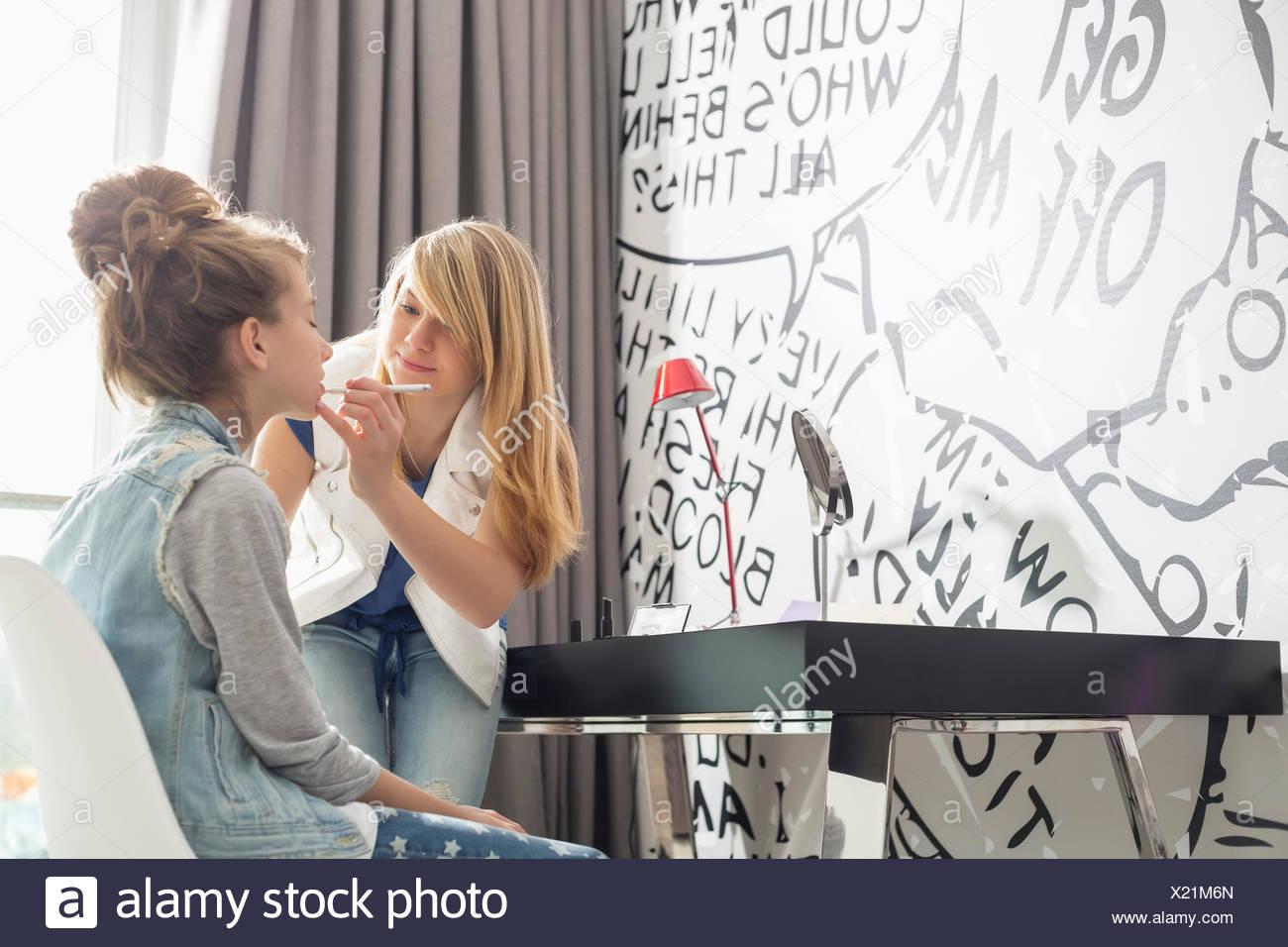 Teenage girl putting lipstick on sister at home - Stock Image