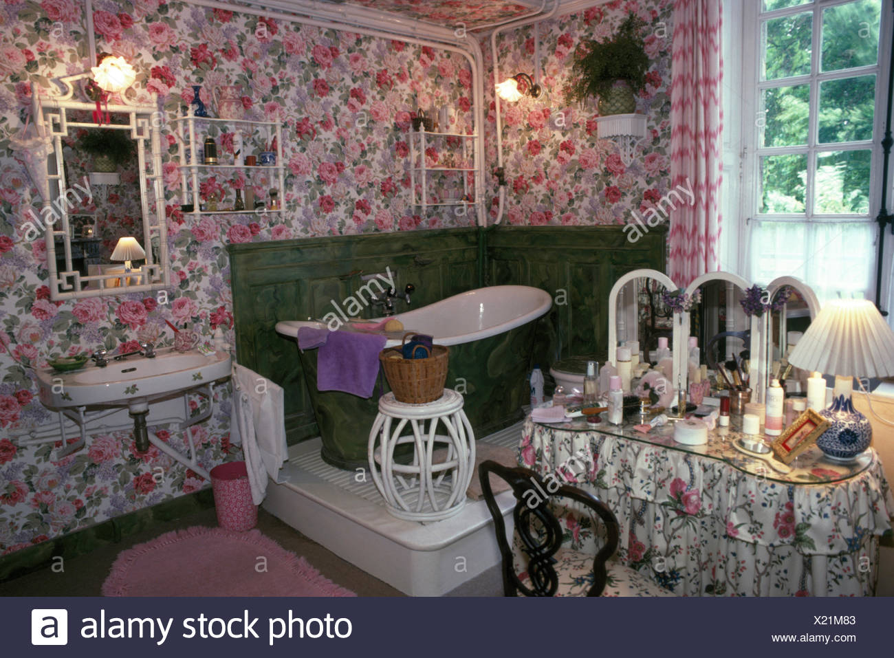 Slipper bath on small platform in corner of eighties bathroom with rose patterned wallpaper - Stock Image