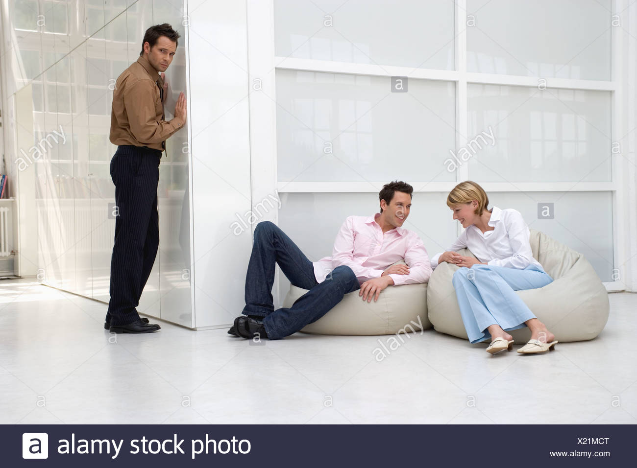 distrustful businessman listening to conversation of two business colleagues relaxing and gossiping - Stock Image