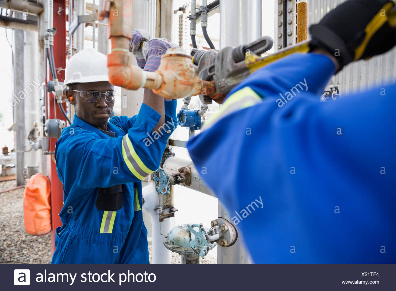 Workers repairing pipe at gas plant - Stock Image