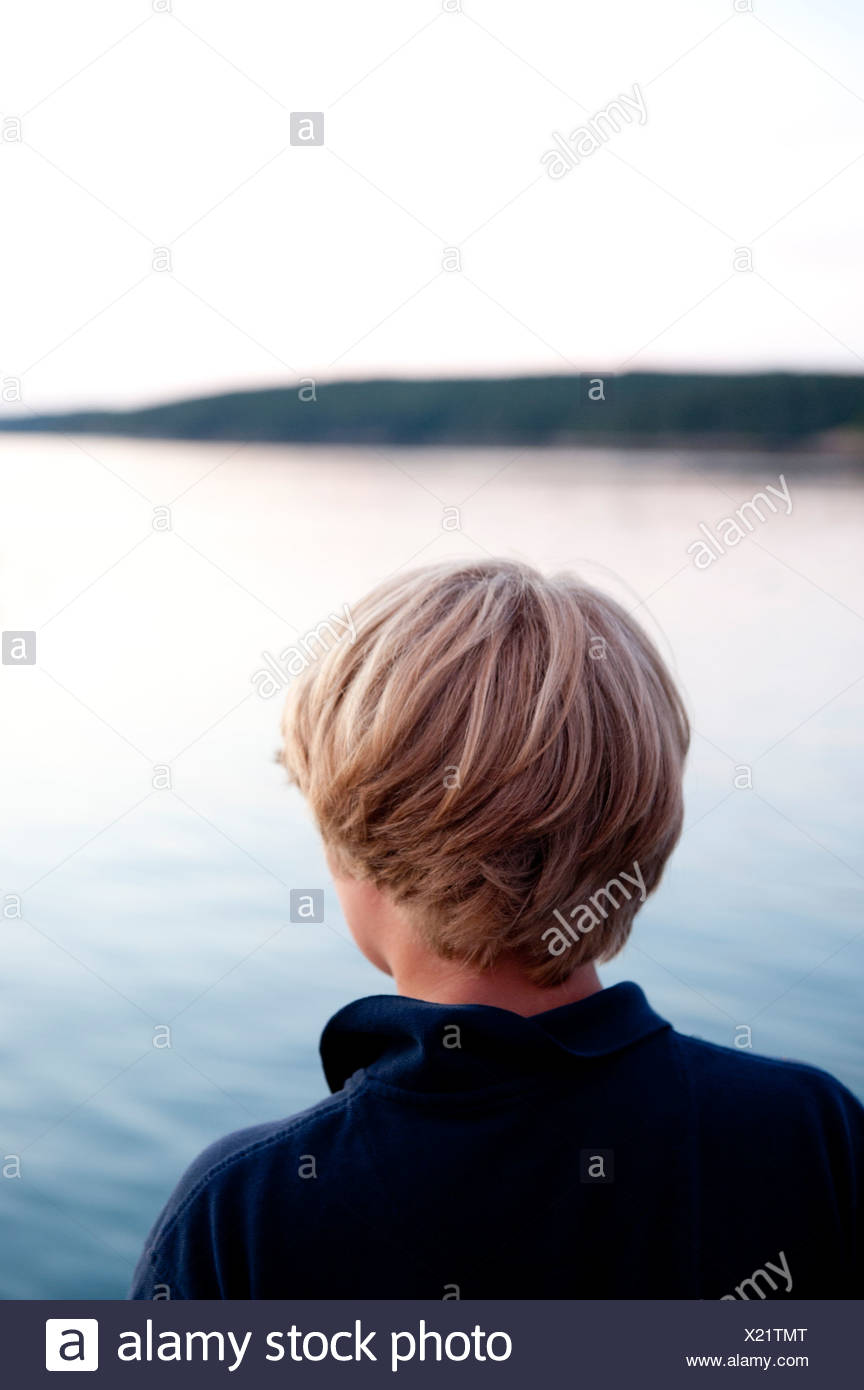 a boy looks out to the sea from an island in maine - Stock Image