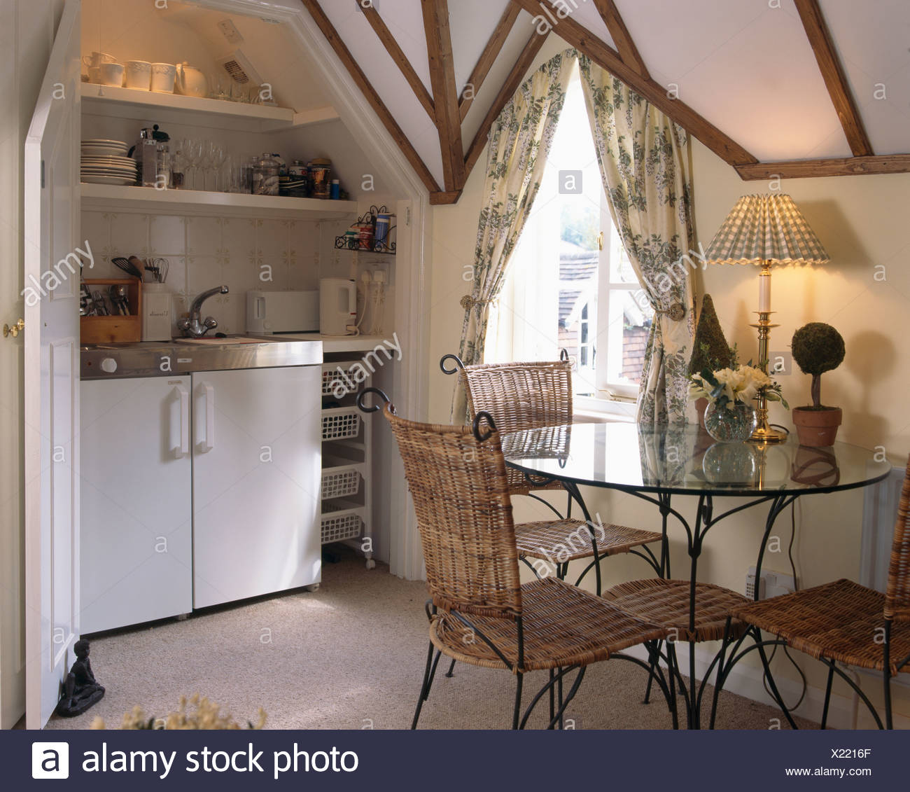 Small Country Table And Chairs: Lighted Lamp On Glass Table And Wicker Chairs In Small Kitchen Dining Room In Country Loft