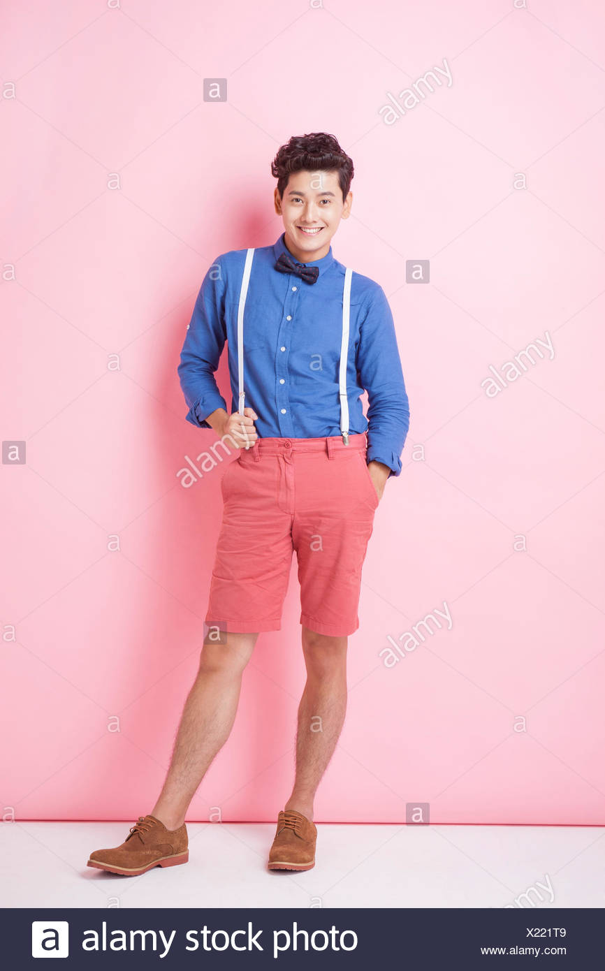 2f754785ccad Young adult man in retro style with bow tie standing on pink background  with his hand in his pocket and on her suspender