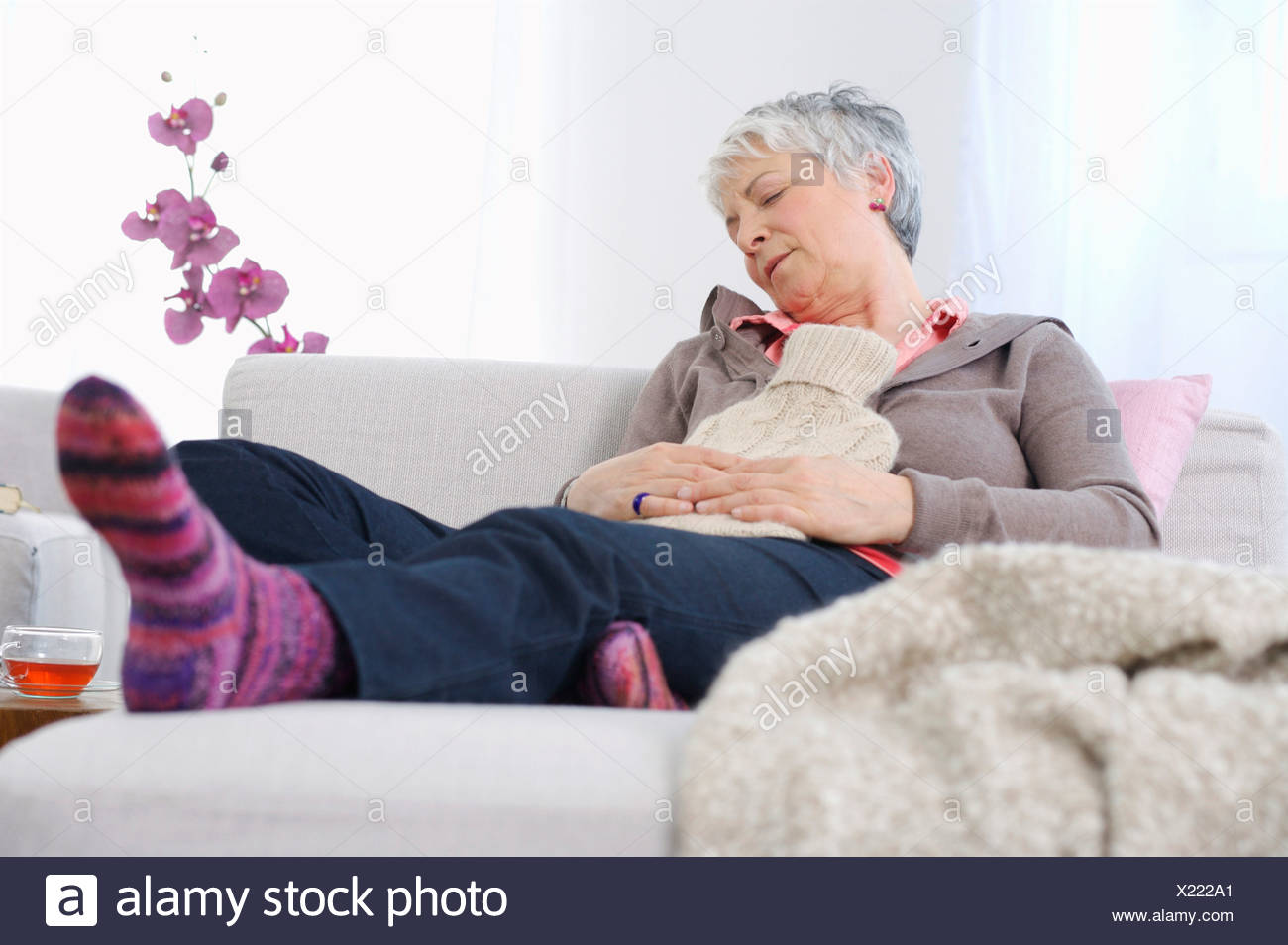 Senior woman resting at home with ice pack on stomach - Stock Image