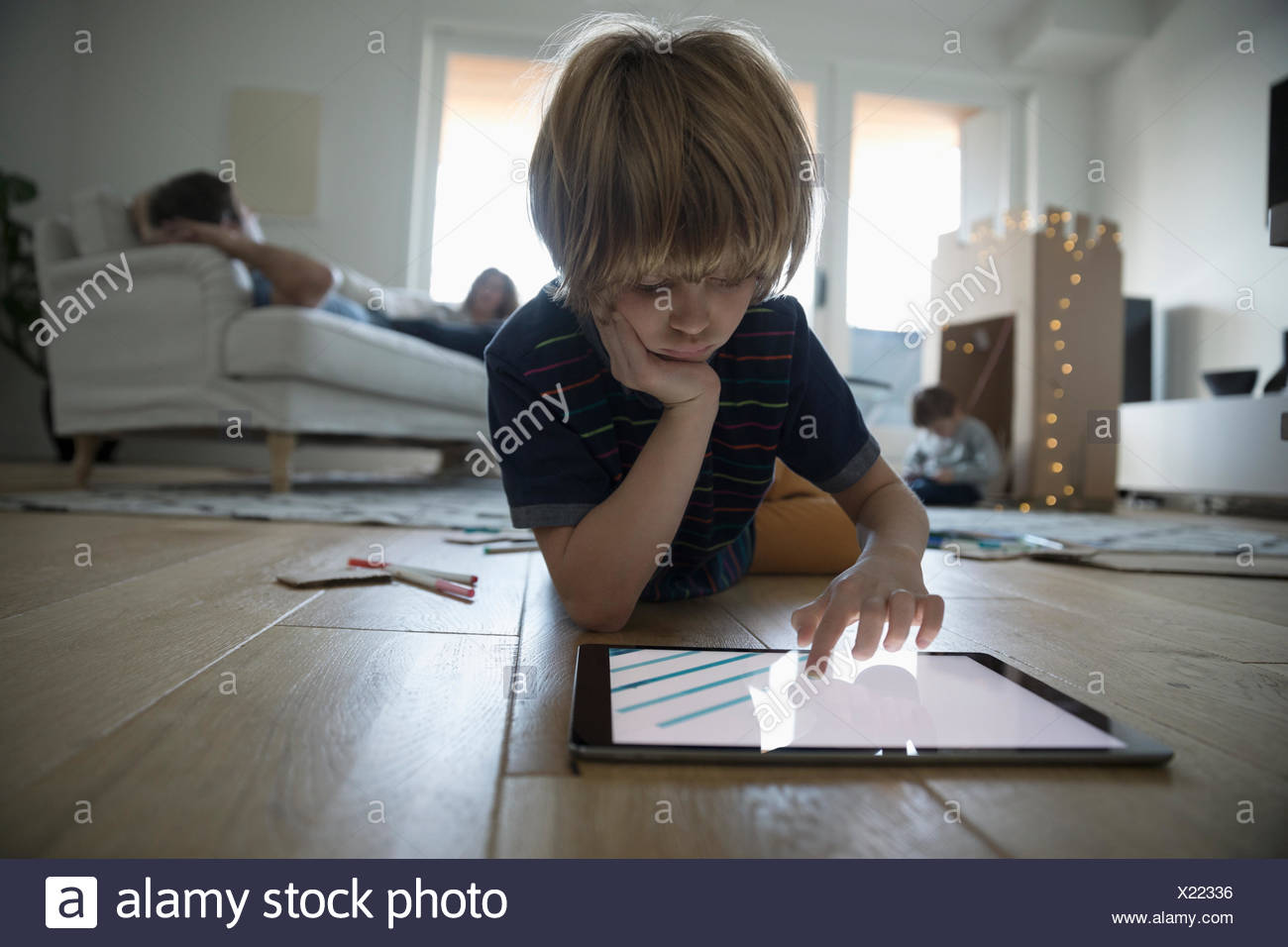 Focused boy drawing with digital tablet on living room floor - Stock Image