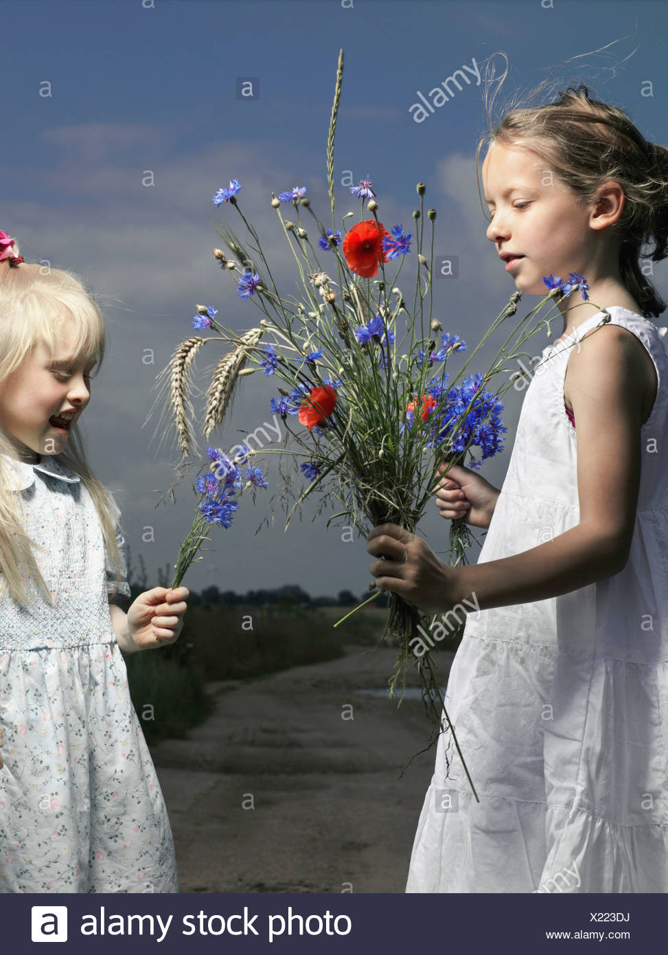 Two girls holding bunches on wildflowers - Stock Image
