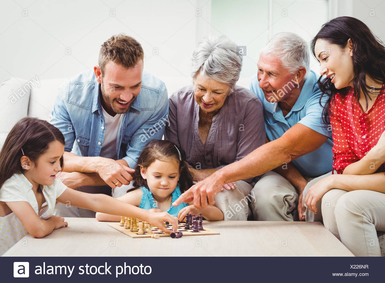Smiling family playing chess - Stock Image