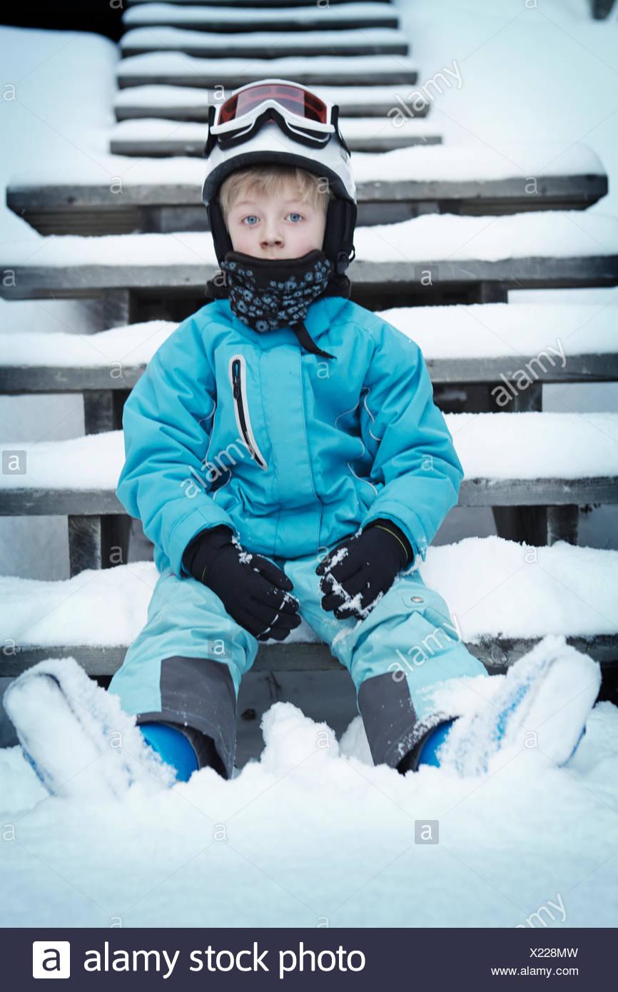 Boy in skiwear sitting on steps in winter - Stock Image