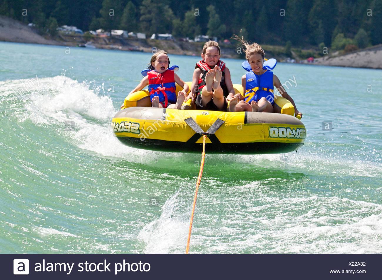 Three children enjoy tubing on Lake Koocanusa, East Kootenays, BC, Canada. - Stock Image