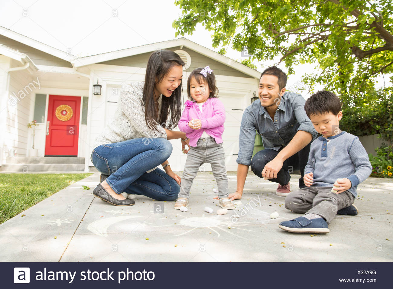 Mid adult couple with two children drawing on paving slabs - Stock Image