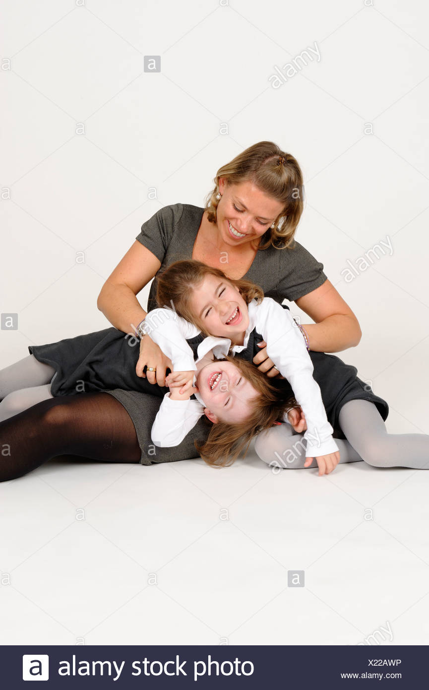 Young girls with her mother, cuddling and having fun, motherly love - Stock Image