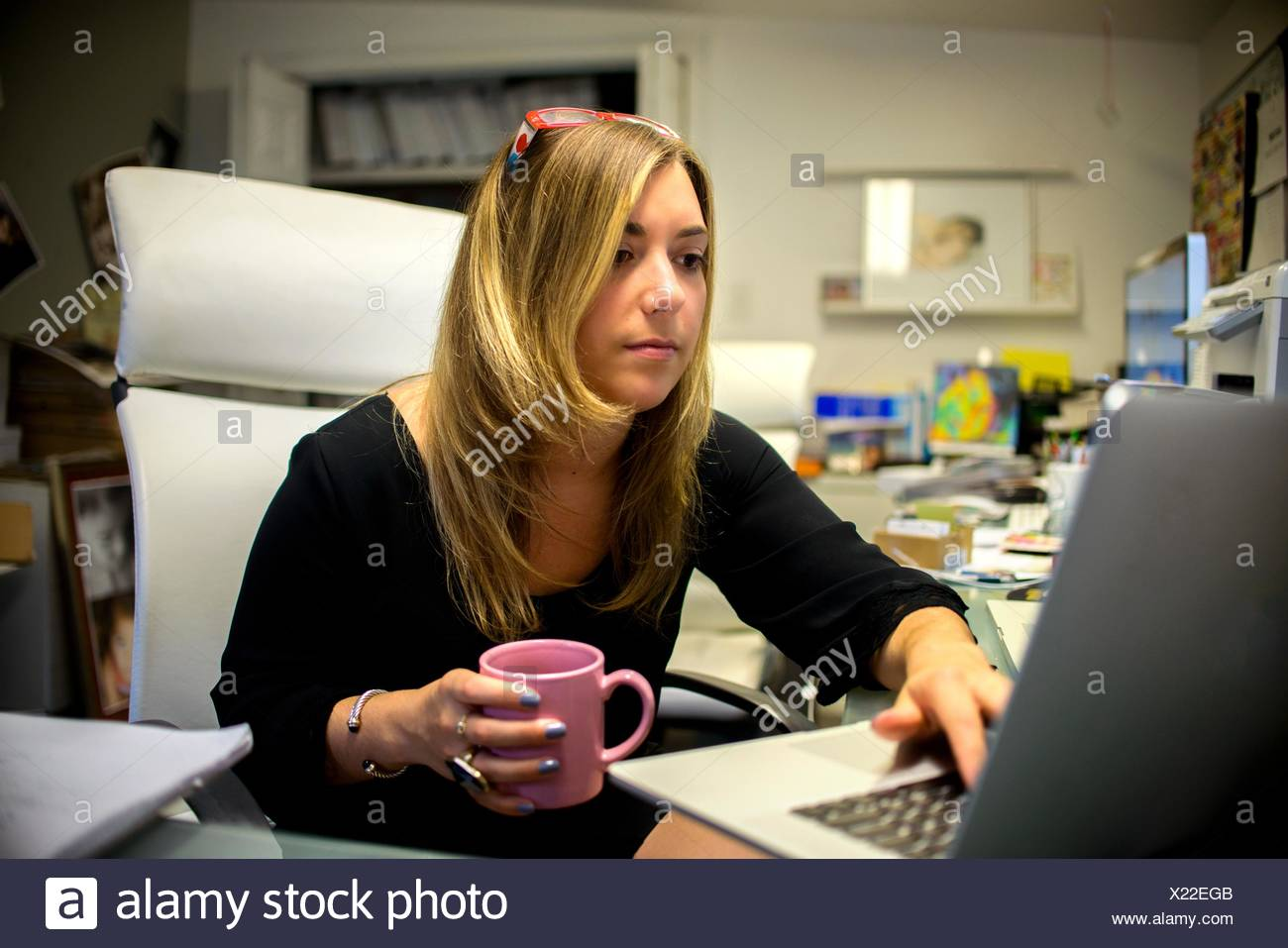 Young woman in office, sitting at desk, holding coffee cup, using laptop - Stock Image