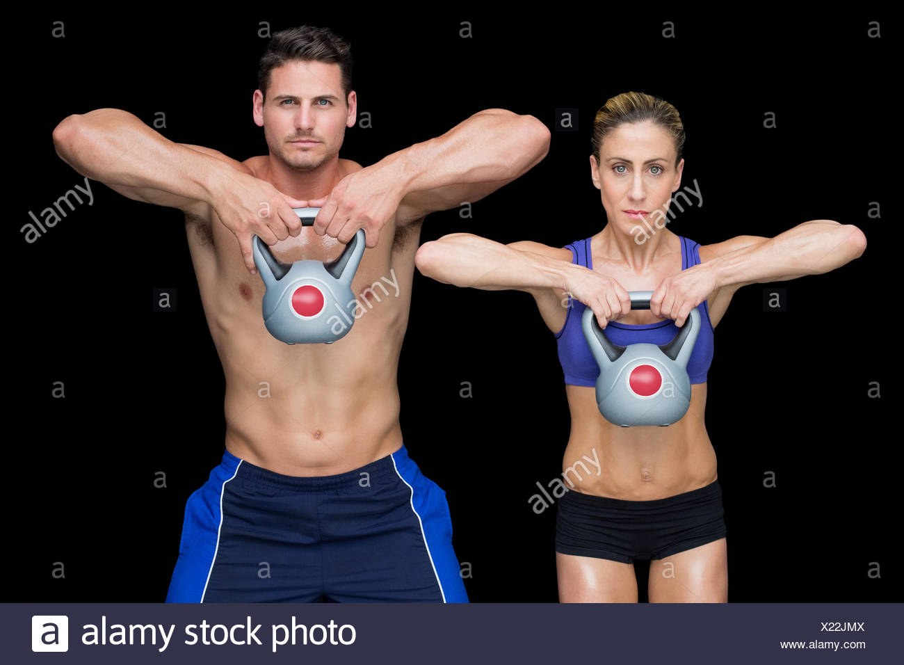 Crossfit couple posing with kettlebells - Stock Image