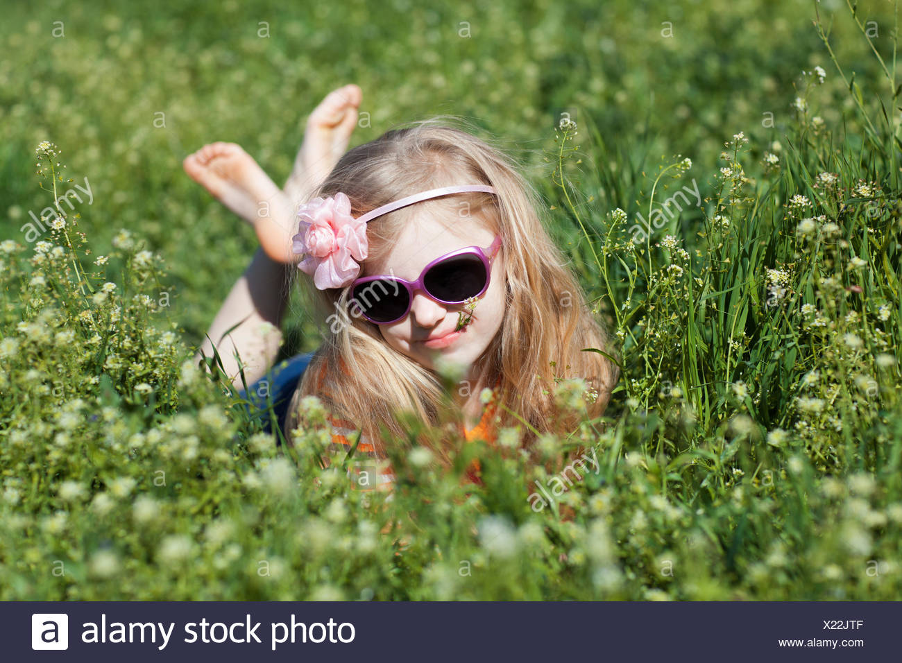 small barefooted girl in grass - Stock Image