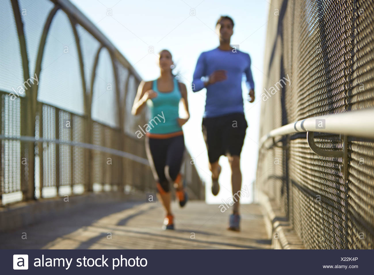 Man and woman running over bridge - Stock Image
