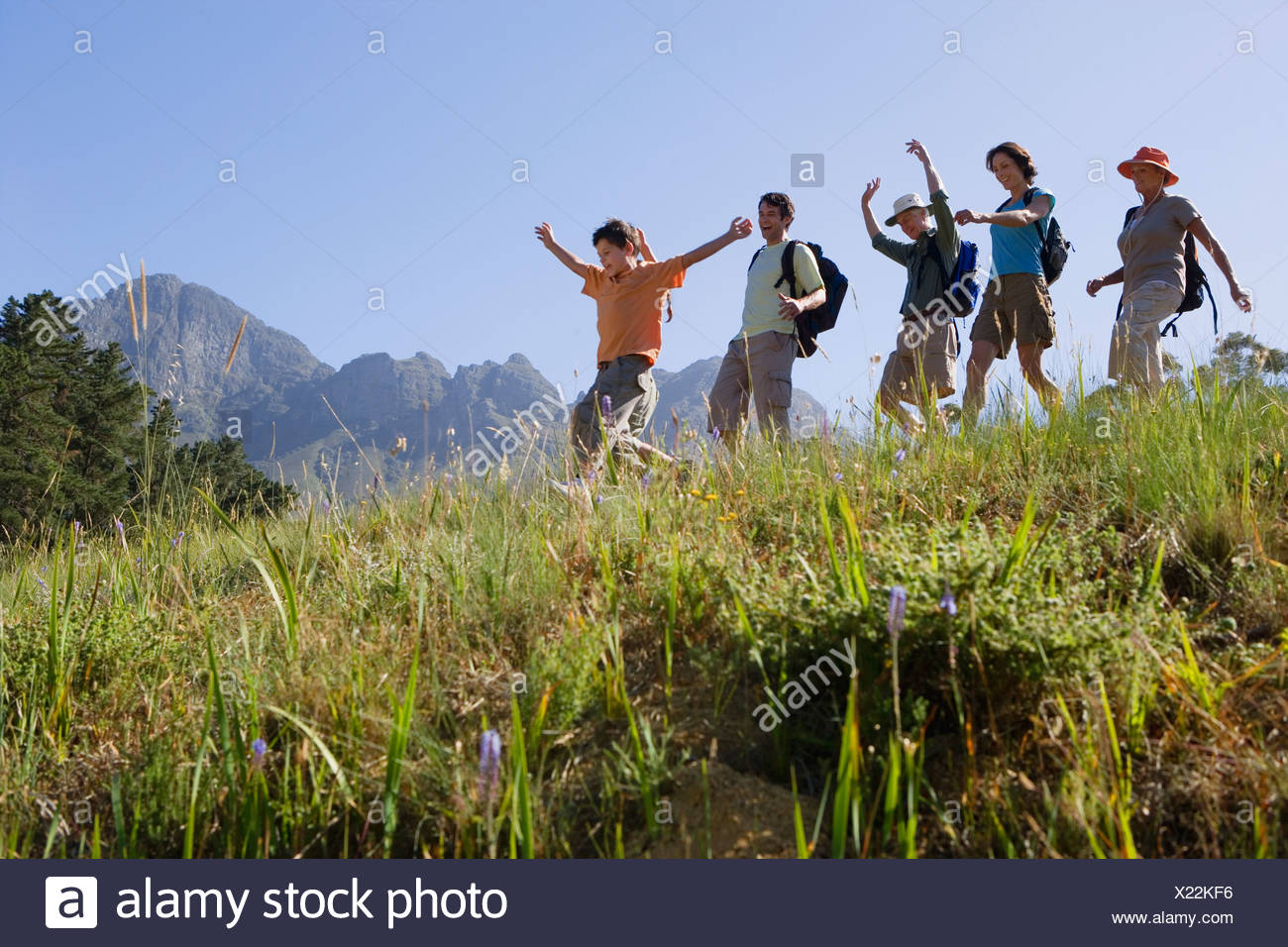 Multi generational family hiking on mountain trail walking in line boy 9 11 leading side view - Stock Image