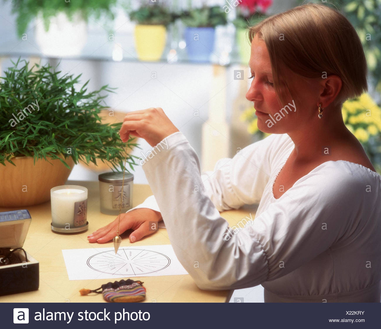 Esotericism, woman, auspendeln, herbs, occultism, spiritualism, occultism, oscillate, swing, parapsychology, pendulum deviation, pendulum, siderisches, herbs, motion, hands, inside - Stock Image