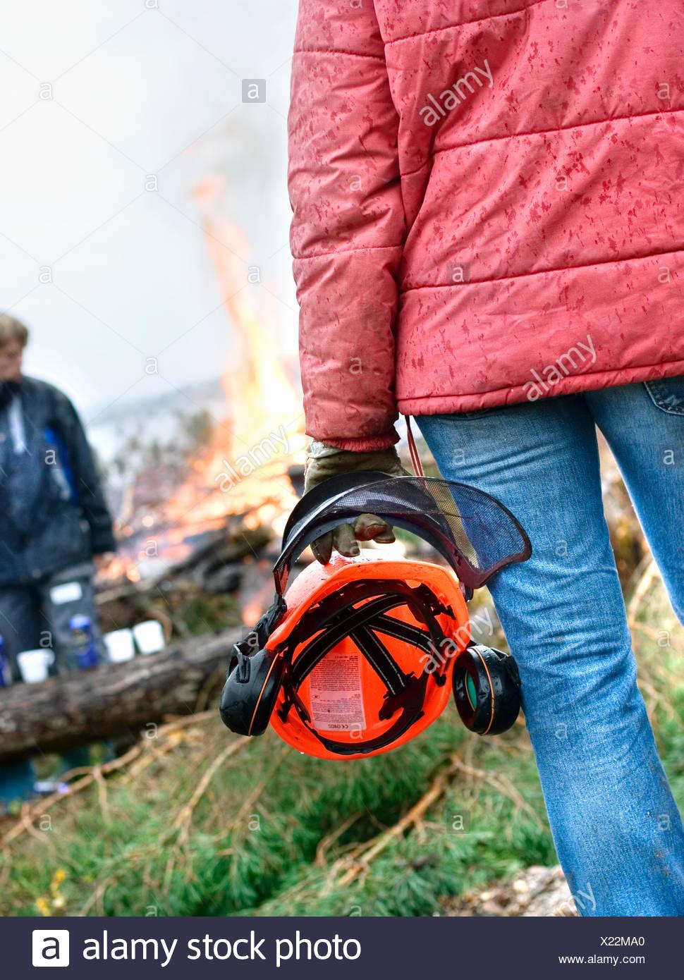 Sweden, Bohuslan, Tjorn, Man holding safety helmet - Stock Image