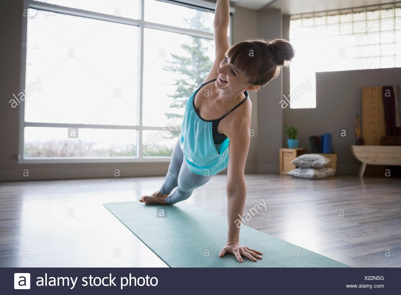 Smiling woman practicing yoga in side plank pose - Stock Image