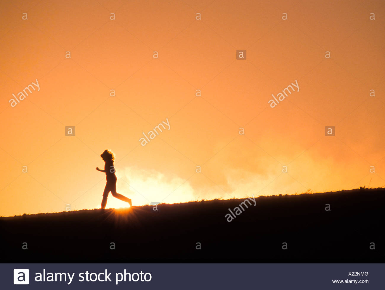 Determined, athletic runner running downhill against sunset in remote area - Stock Image