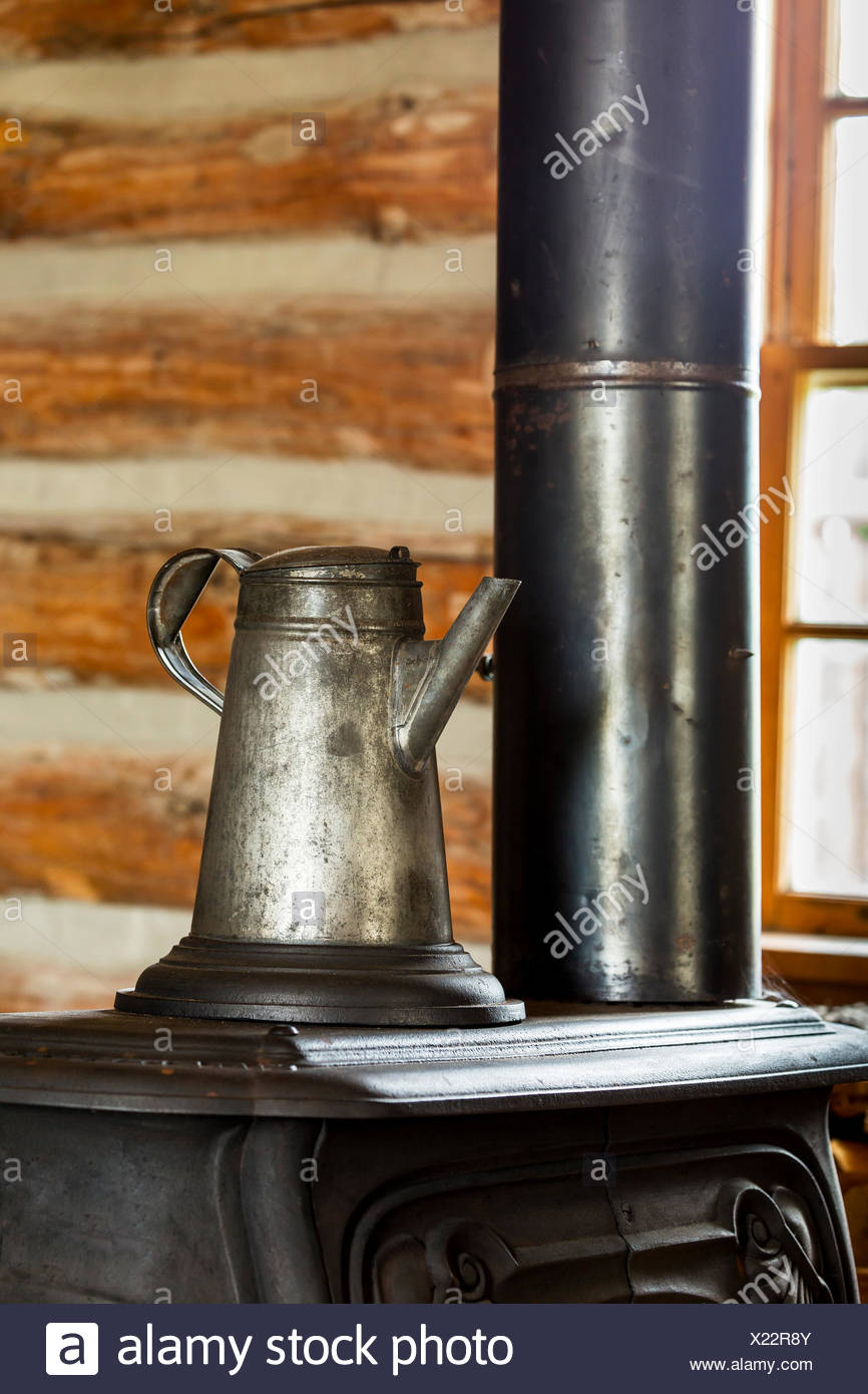 Close up of an old metal coffee pot on top of an old cast iron stove in log cabin with window in the background, South of Maple Creek; Alberta, Canada - Stock Image
