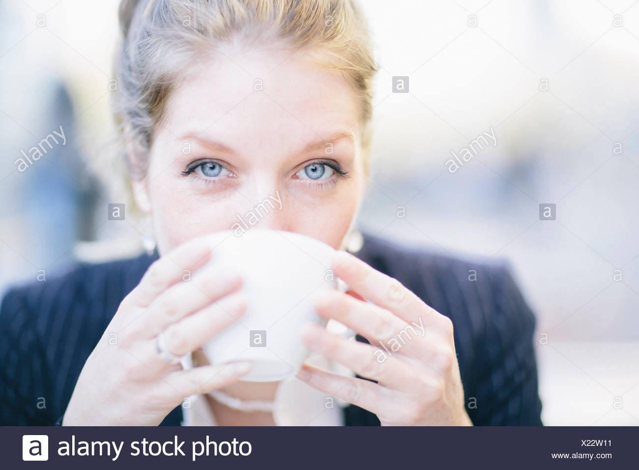 Businesswoman drinking coffee, looking at camera - Stock Image