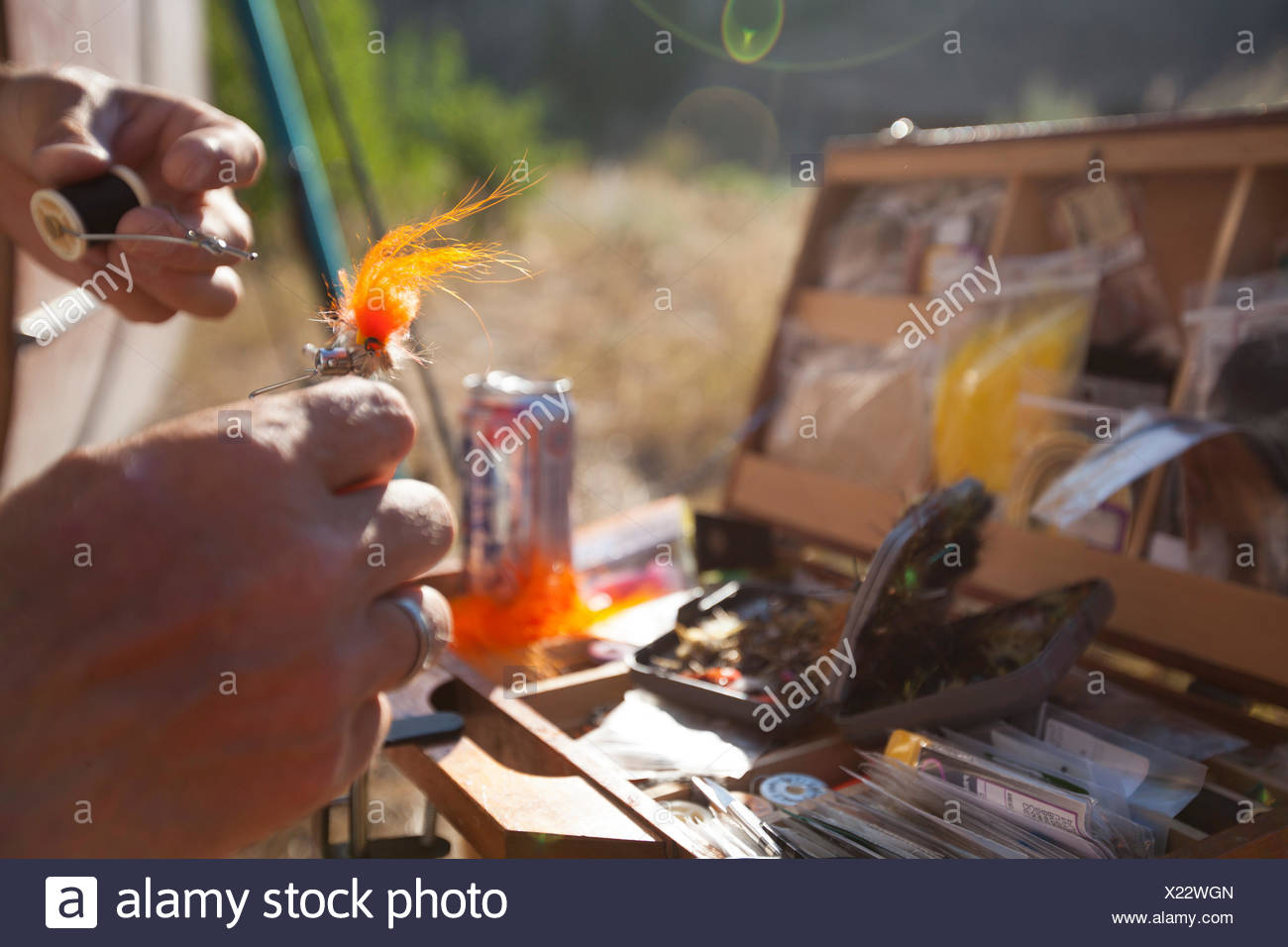 A Man consults the library and ties on a fly before a late afternoon fish on the Big Wood River near Ketchum Idaho. Stock Photo