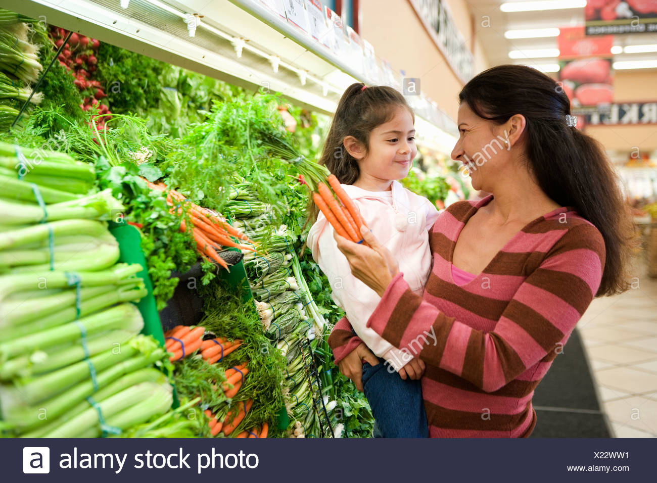 Mother and daughter 4 6 shopping in vegetable section of supermarket woman holding carrots - Stock Image