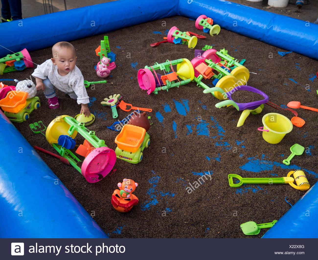 A baby plays in an inflatable sandbox surrounded by toys. - Stock Image