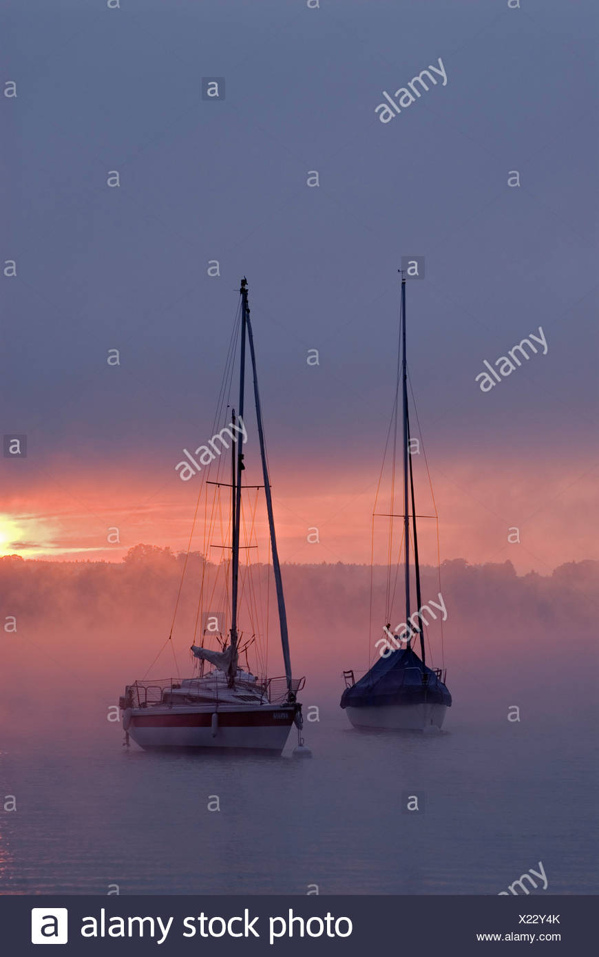 Sun rising behind sailing boats and fog over Ammersee lake, Bavaria, Germany, Europe Stock Photo