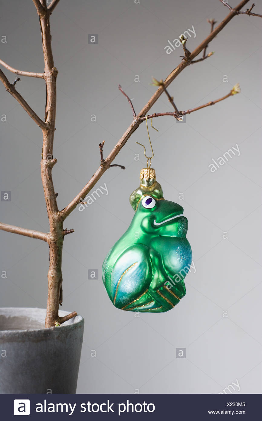 Christmas bauble hanging off a bare tree - Stock Image
