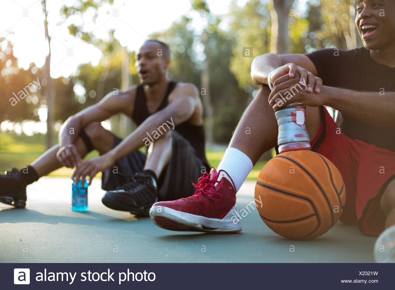 Two young men taking a water break while playing basketball in the park at sunset - Stock Image