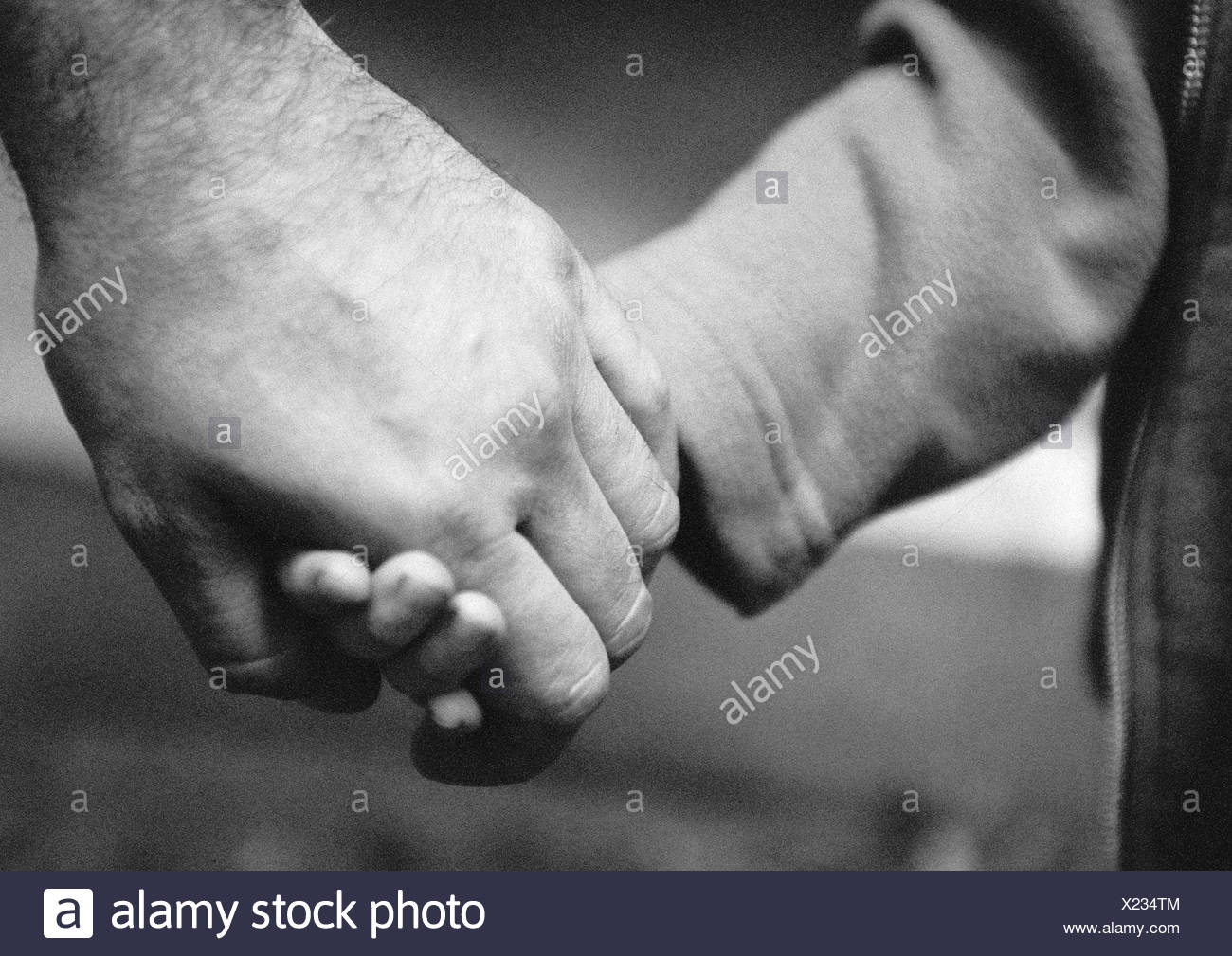 Adult's hand holding child's hand, close-up, b&w - Stock Image