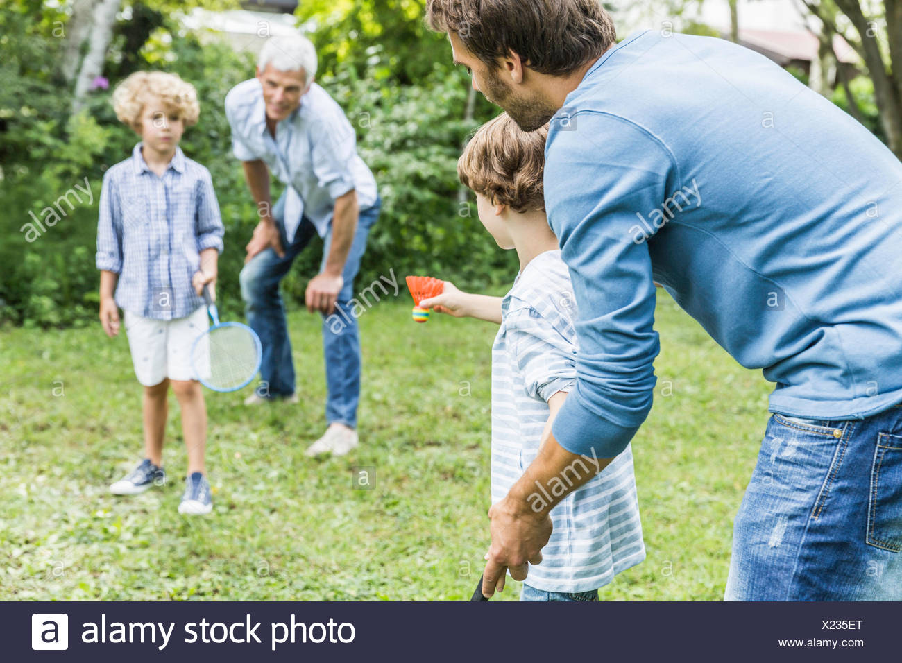 Mature man and son teaching grandsons badminton in garden - Stock Image