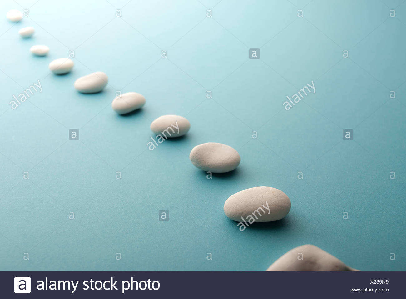 White stones all lined up in perspective - Stock Image