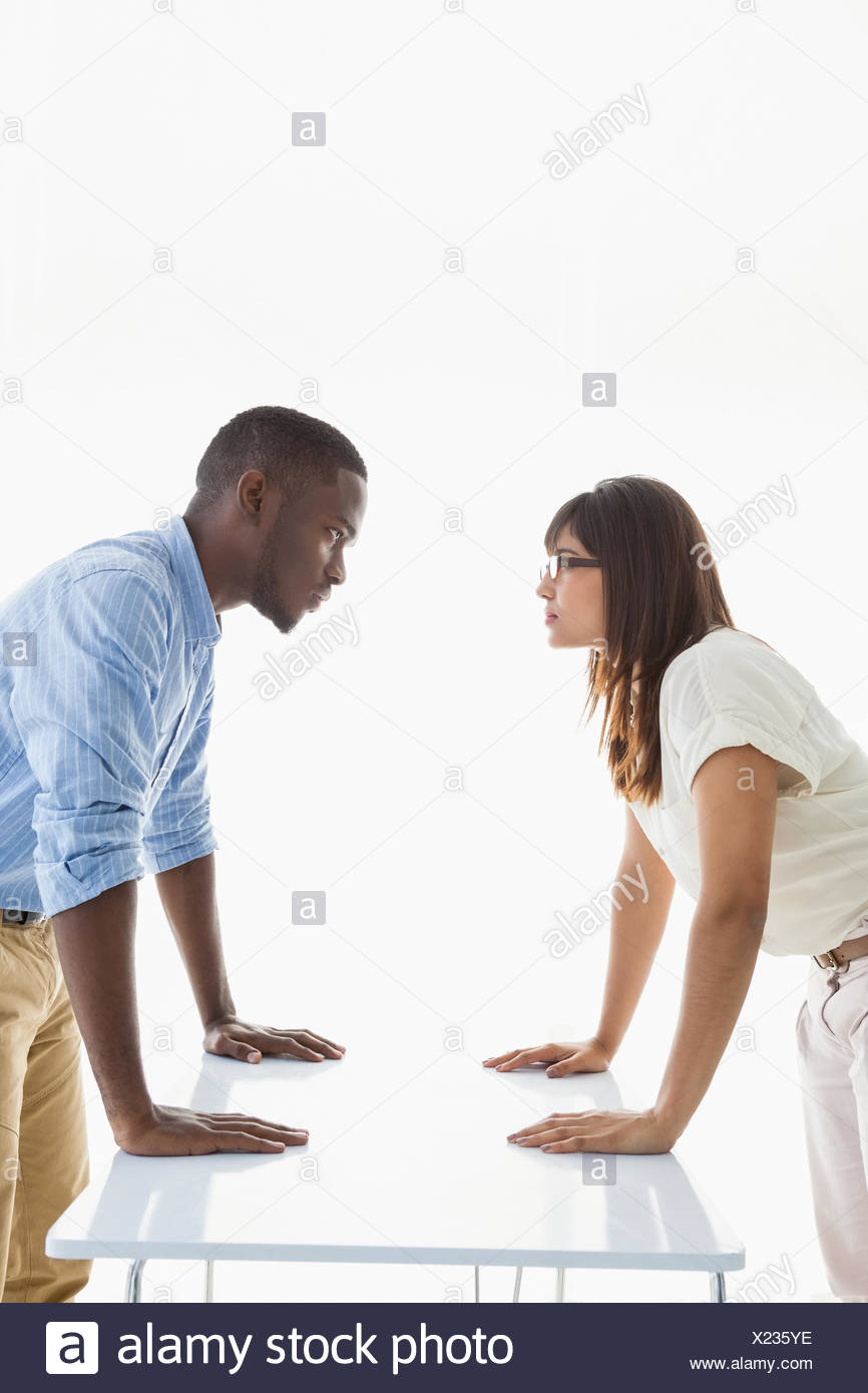 Business people having a stand off at their desk - Stock Image