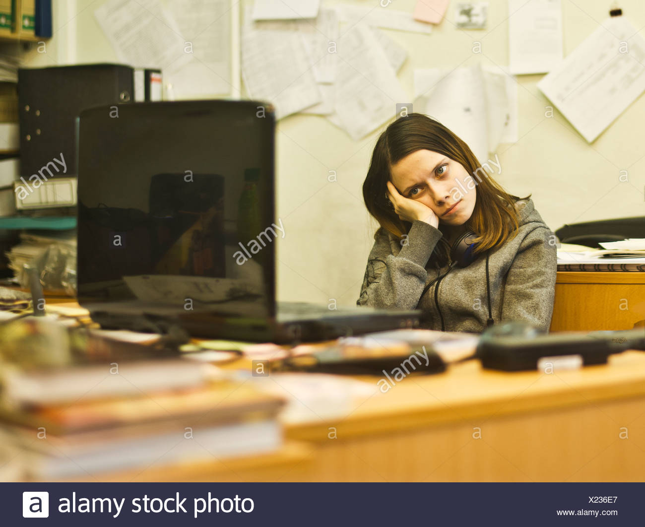 Bored young woman at desk leaning on elbow - Stock Image