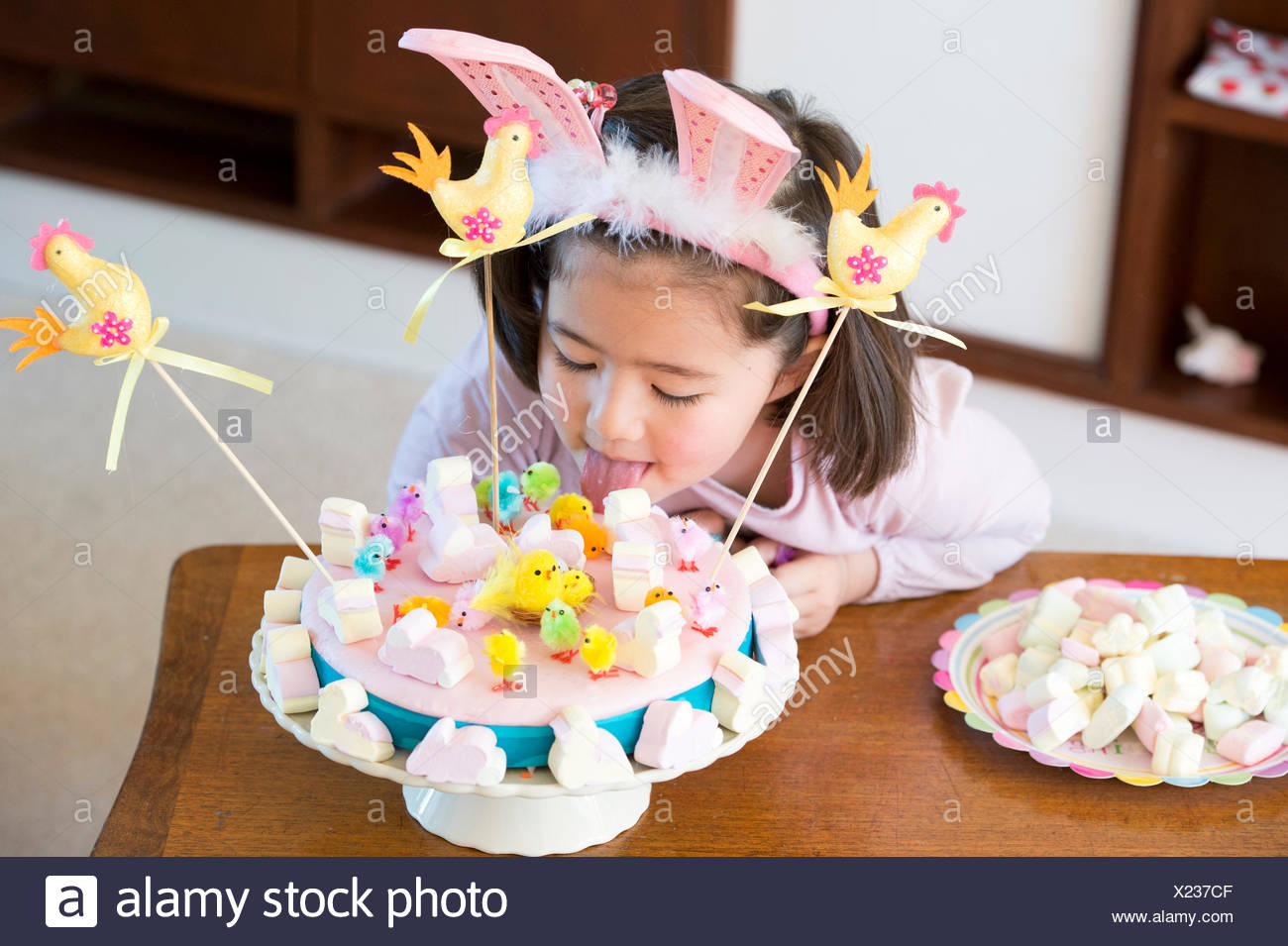 Young girl licking cake on table - Stock Image