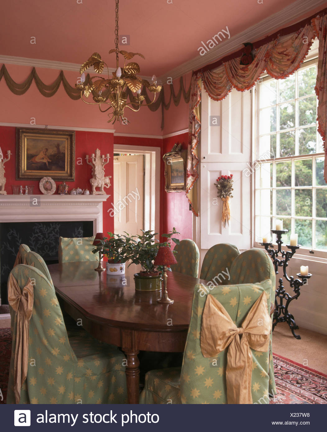 Green Loose Covers With Silk Bows On Chairs At Table In Red Nineties Dining Room A Brass Light Fitting